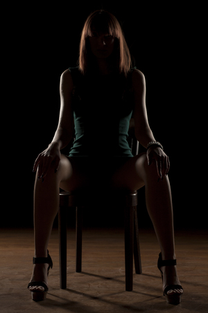 spread legs: woman sitting on a chair in the dark with spread legs Stock Photo