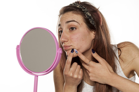 acne: young woman squeezing her acne in front of a mirror