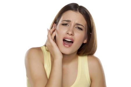 dolor de oido: hermosa mujer joven tiene dolor en el o�do