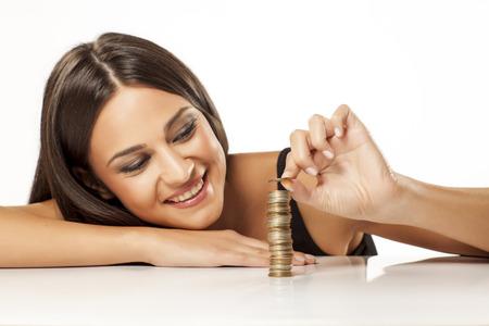 happy attractive girl arranging coins in column