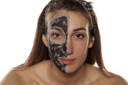 mud woman: young woman with mud mask on half of her face