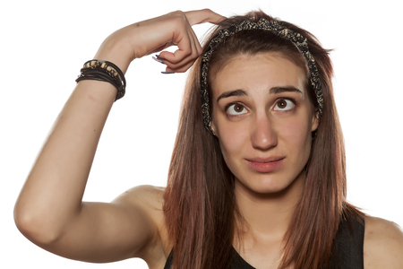 young confused girl with crossed eyes scratching her head