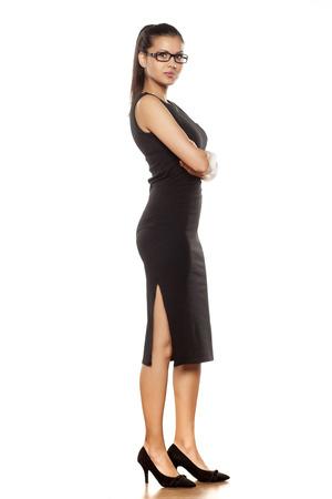 mujeres morenas: mujer joven con gafas posando en un vestido negro ajustado sobre un fondo blanco