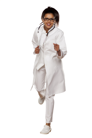 young woman doctor running on a white background