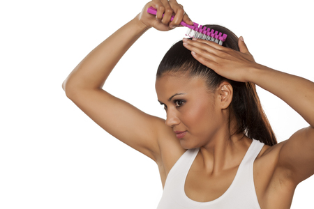 pony tail: young beautiful woman adjusts her pony tail Stock Photo