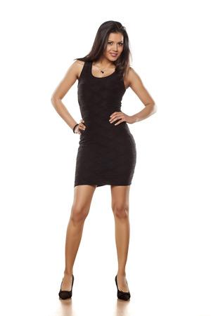mujeres morenas: joven y bella mujer posando en apretado vestido negro corto y tacones altos Foto de archivo