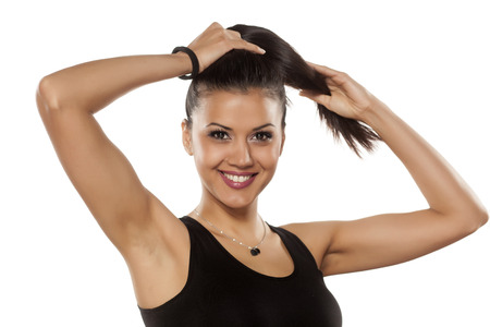 femmes souriantes: très heureux peau foncée belle jeune femme tenant sa queue de cheval Banque d'images
