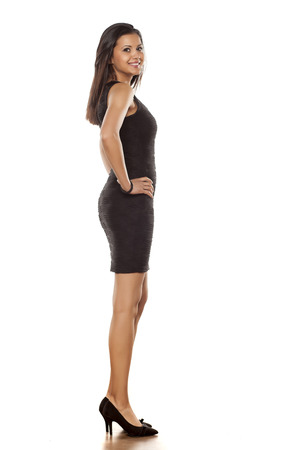 side view of a young beautiful lady posing in short black tight dress Stock Photo