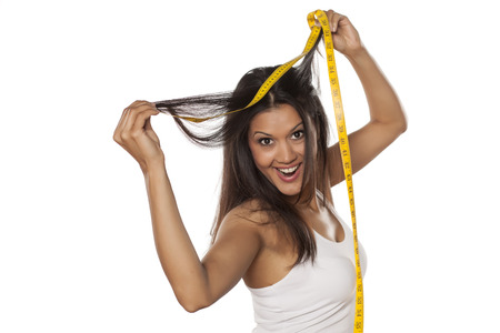 sexy latina: young happy woman shows the length of her hair