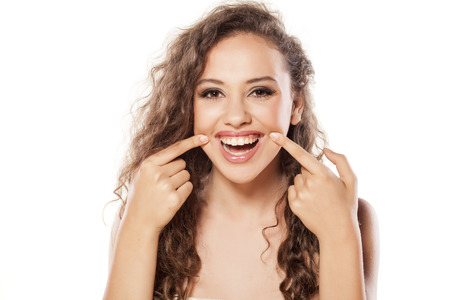 induce: Smiling girl with wavy hair holding the edges of her lips with her fingers