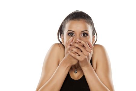 mujeres morenas: Hermosa sorprendió a mujer joven de piel oscura que cubre la boca con las manos Foto de archivo