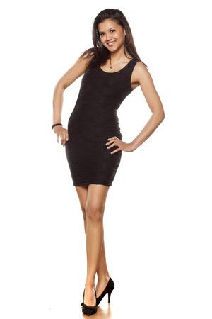 mujeres morenas: joven y bella mujer posando en un vestido ajustado negro corto y tacones altos