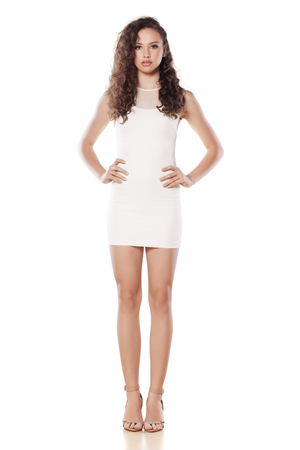 Pretty girl in short white dress, wavy hair and high heels posing on white background Stock Photo