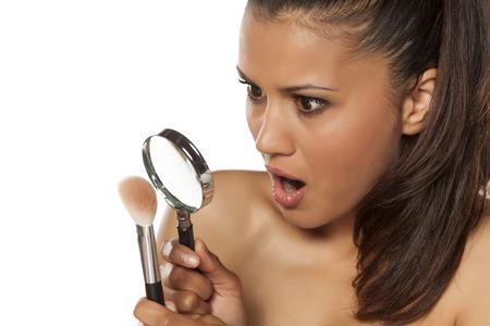 gitana: mujer joven sorprendido mirando su pincel de maquillaje a través de la lente