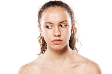 looking aside: Serious young girl without makeup looking aside on a white background