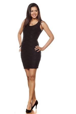 femmes souriantes: belle jeune femme posant enfin serré robe noire et talons hauts Banque d'images
