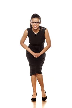 mooie jonge vrouw in een strakke zwarte jurk heeft een behoefte om te urineren