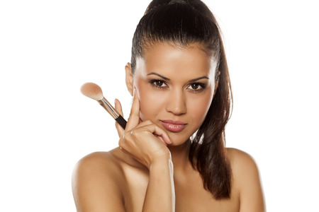 ethnic woman: a young Indian woman posing with a brush for makeup