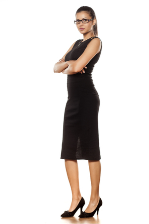 sexy woman standing: beautiful young woman with glasses in tight black dress posing in the studio