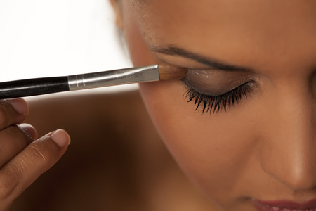 woman shadow: woman applying eye shadow with a brush - close up