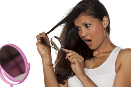 shocked young woman looking at her damaged hair with magnifying glass