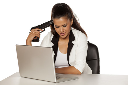 holding gun to head: desperate young woman on a laptop holding a gun to her head