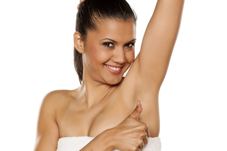 smiling young ethnic woman showing her shaved armpit and showing thumb up Banque d'images
