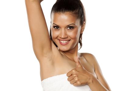 Lachende jonge etnische vrouw die haar geschoren oksel toont en duim toont Stockfoto