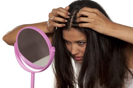 彼女の髪の根を見て若い女性 写真素材