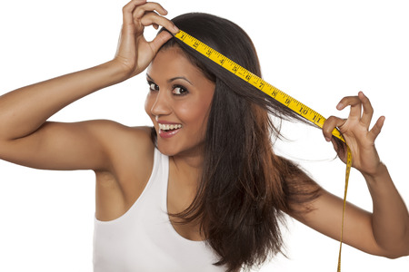 sexy latina: young happy woman holding measuring tape and showing the length of her hair