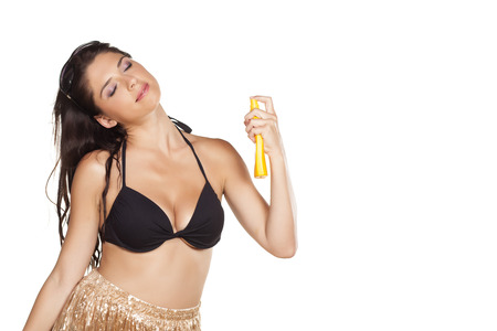 suncare: Smiling pretty girl applying sunscreen spray