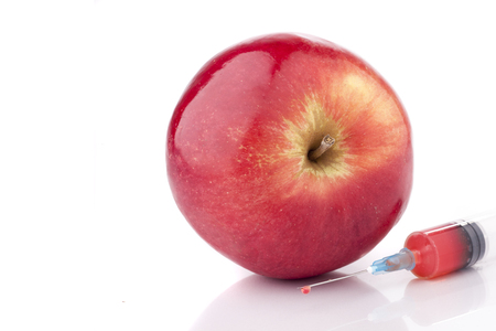 Big fresh red apple with a syringe. Concept for GMO