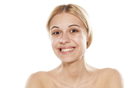 Beautiful young woman with a fake smile on white background Stock Photo