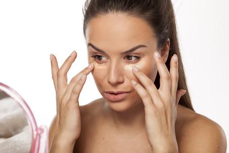 그녀의 얼굴에 액체 기초의 다른 그늘을 적용하는 여자