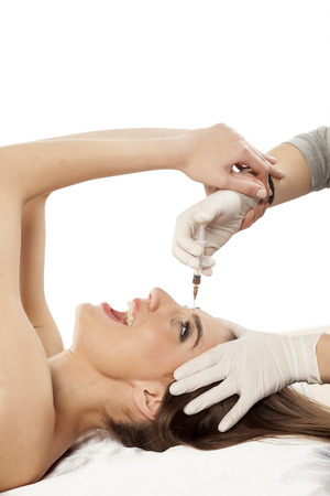 scared young woman resisting injection of botox in her forehead Stock Photo