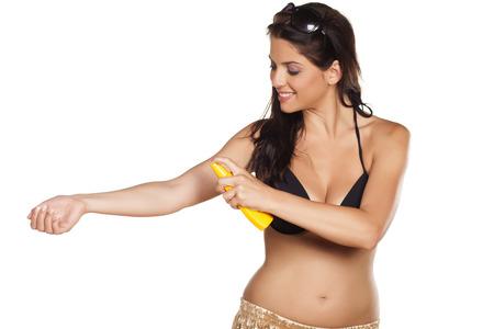 suncare: Smiling pretty girl applying a sunscreen spray