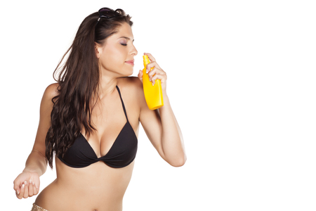 suncare: smiling beautiful girl enjoying the scent of her sunscreen Stock Photo