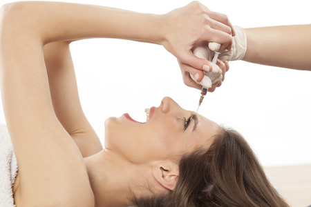 counteract: scared young woman resisting injection of botox in her forehead Stock Photo