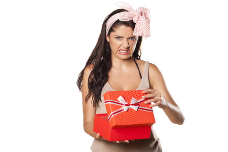 pretty girl with a scarf on her head is not happy and is disgusted from her gift Stock Photo