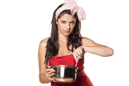 desconfianza: housewife preparing meal in a pot, and looking with distrust
