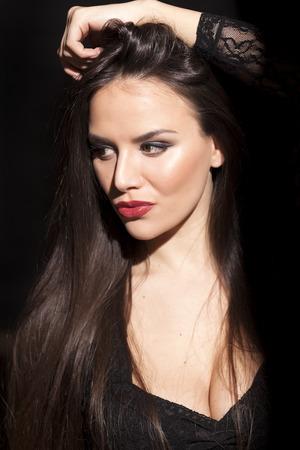 neckline: Pretty young woman with deep neckline posing on a dark background