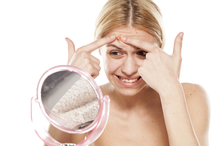 young woman squeezing apimple on her forehead in front of a mirror