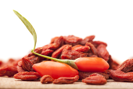pile of dry and fresh goji berries on a white background