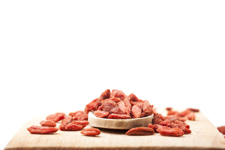 chinese wolfberry: pile of dried goji berries on a wooden spoon on a white background