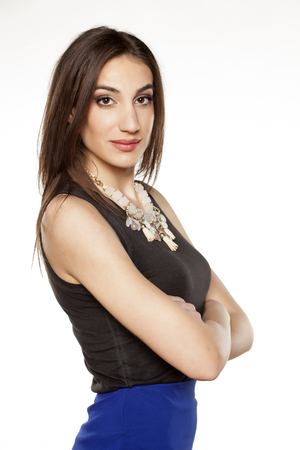 neckless: elegant young woman in black sleeveless shirt and neckless posing with crossed arms