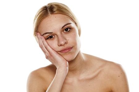 portrait d'une jeune femme ennuyé sans maquillage sur un fond blanc Banque d'images