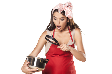 concep: shocked housewife looking at pot with food through magnifying glass