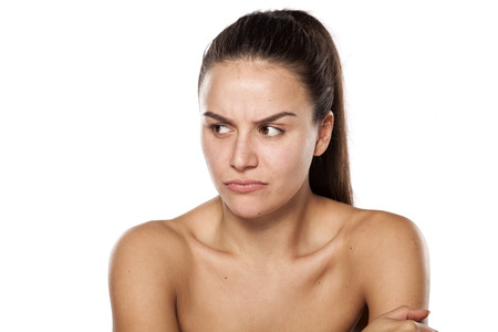 scowling dissatisfied young woman without makeup