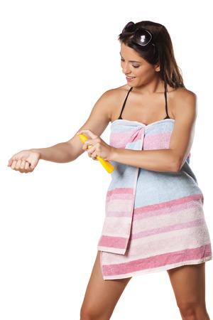 suncare: Smiling and pretty girl appliying sunscreen spray