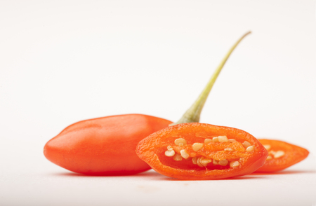 chinese wolfberry: whole and halved grain of fresh goji berry on white background